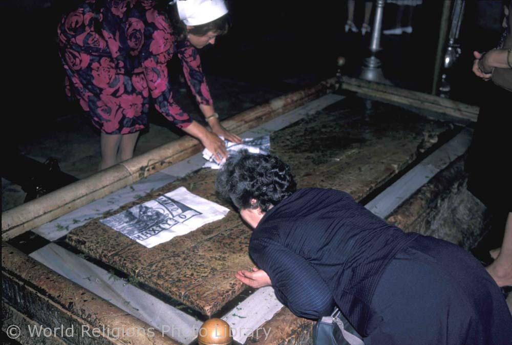 Italian pilgrims pressing material into the `stone of unction` Holy Sepulchre church Jerusalem