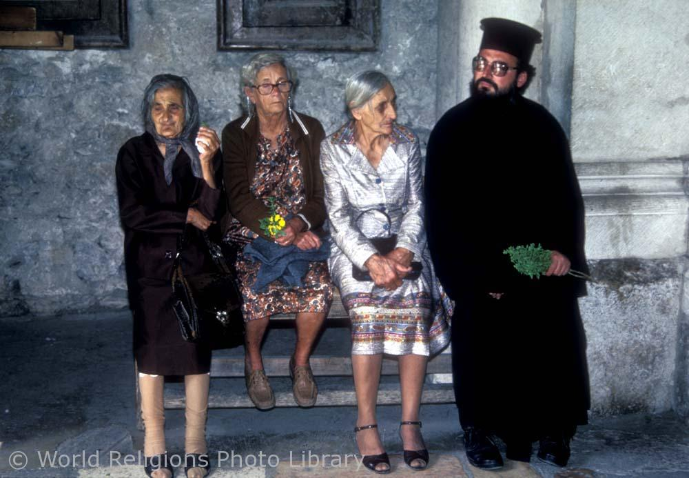 Greek Orthodox pilgrims rest tired feet at the entrance to the Church of the Holy Sepulchre