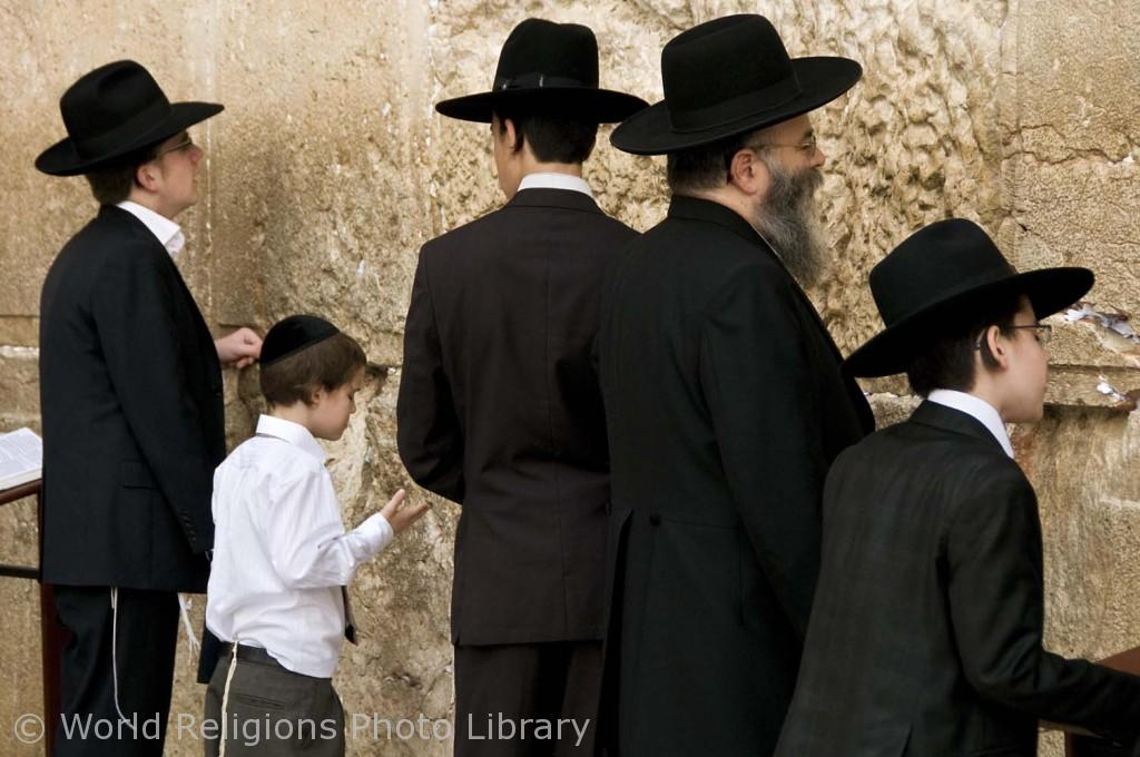 Orthodox Jewish men pray at the Western Wall