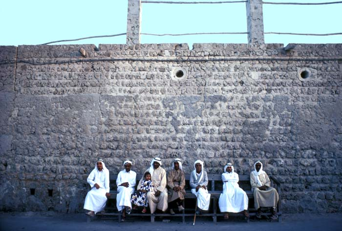 Arab men and a girl sitting on a street bench in Ajman during the fast month of Ramadan