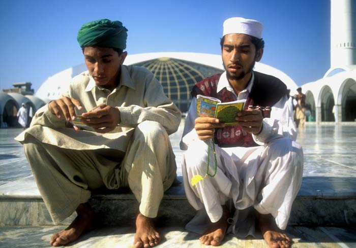 Two Pakistani youth studying the Qur`an at the Lal Hussein shrine in Lahore