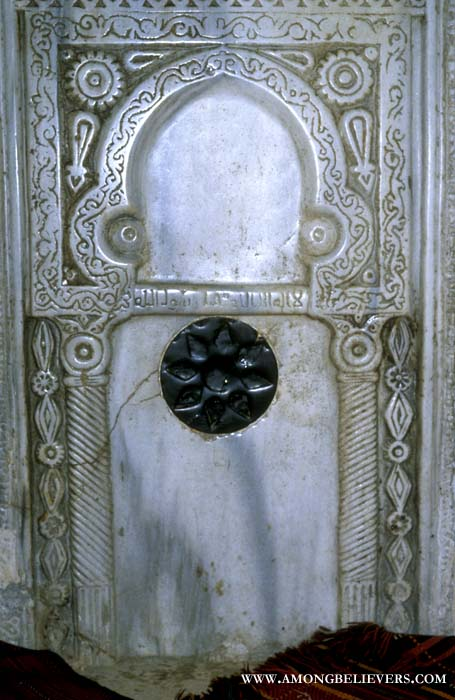 Tiny marble prayer niche of mihrab beneath the rock.